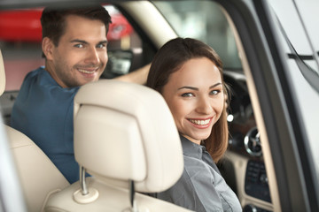 Feeling happy in their new car. Beautiful young couple sitting a