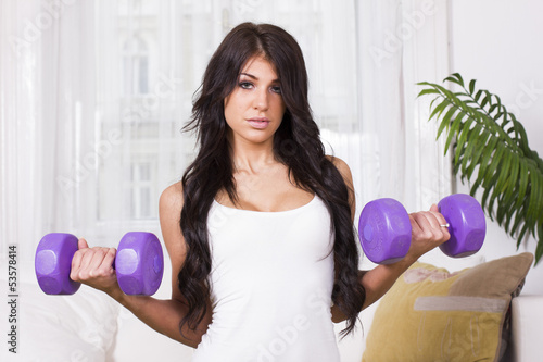 Young beautiful woman doing training with weights at home
