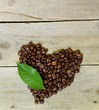 coffee beans in the shape of heart on a wooden background