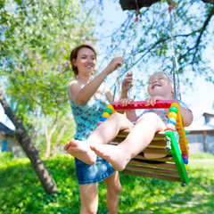 Happy mother rocking a laughing baby on a swing