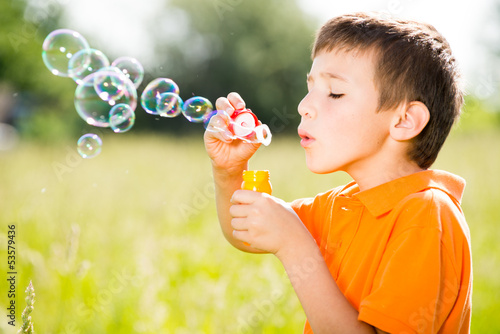 Young caucasian boy blowing the soap bubbles on nature