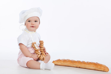 Little baker baby girl with a long loaf and bagels, isolated on