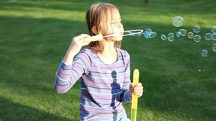 child blowing soap bubbles in spring park.