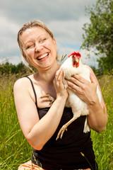 Frau mit Huhn im Arm lacht