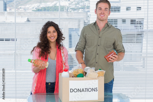 Smiling volunteers taking out food from donations box