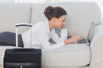 Business woman lying on couch with laptop and suitcase