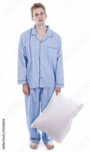 Exhausted man in pajamas holding pillow