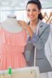 Smiling fashion designer adjusting dress