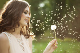 Beautiful woman blowing a dandelion