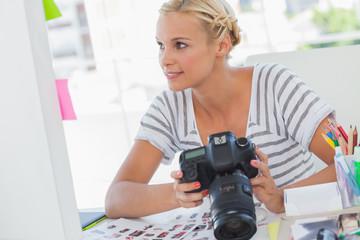 Pretty photo editor looking at a digital camera