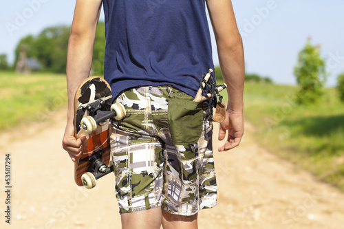 Boy with skateboard and slingshot in pocket