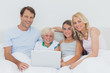 Smiling family using a laptop together