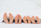 Family on the bed showing their feet