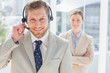 Handsome call centre agent with colleague behind him