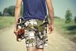 Boy with skateboard and slingshot in pocket on rural road