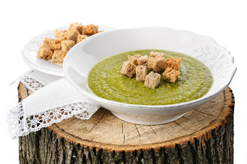 Green pea soup with croutons on the wooden stump
