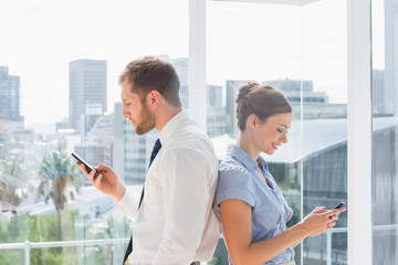 Business team standing back to back and texting