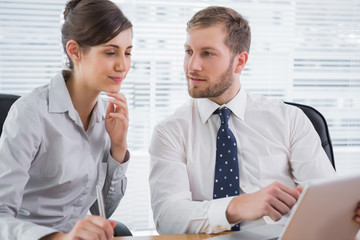 Businessman pointing to laptop with colleague