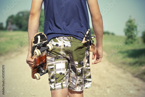 Boy with skateboard and slingshot in pocket on rural road