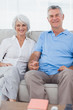 Mature couple hand in hand sitting on a couch