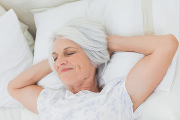 Peaceful woman relaxing in bed
