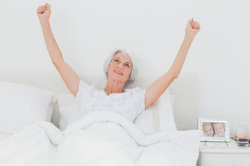 Woman waking up and raising arms in bed