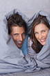 Delighted couple having fun wrapped in their duvet