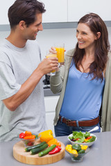 Lovely couple clinking glass of orange juice