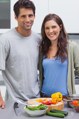 Cheerful couple smiling at camera and preparing vegetables