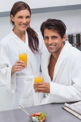 Lovely couple wearing bathrobes and holding glass of orange juic