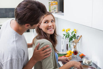 Delighted couple cooking in kitchen