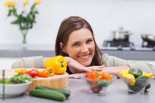 Cheerful woman leaning on the counter of her kitchen