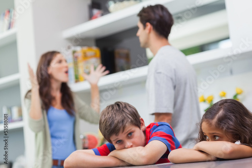 Couple arguing behind their children