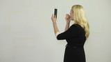 Businesswoman with lipstick using electronic tablet as mirror
