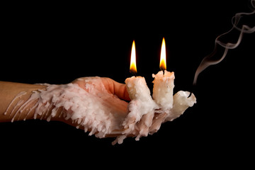 Three candle sticks on fingers buring smoulder