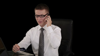 Young businessman with credit card on the phone
