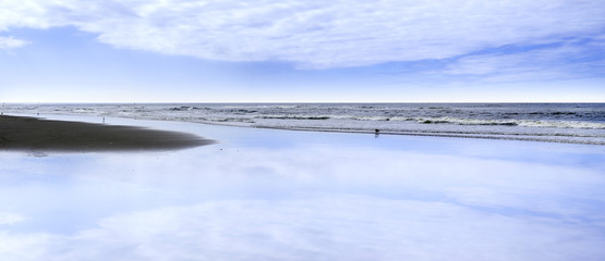 Beach in scheveningen with clouds reflecting in the water