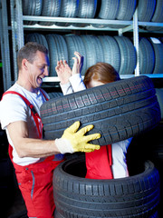 Ridiculous motor mechanic in a garage has a lot of fun at work