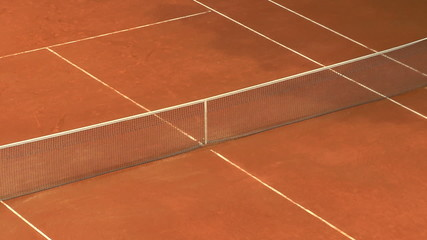 Balls bouncing on orange clay tennis court