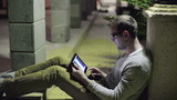 Young man working with tablet computer at night garden