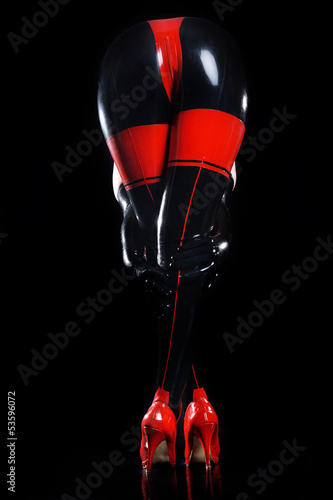 canvas print picture Sexy Frau mit Lackanzug beugt sich