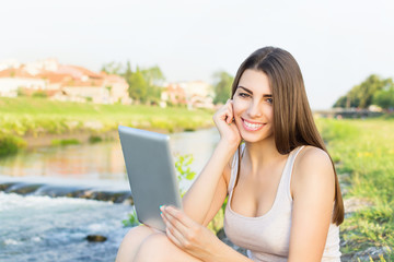 Beautiful young woman sitting by the river using tablet computer