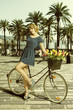 blonde woman in sexy pose near bicycle