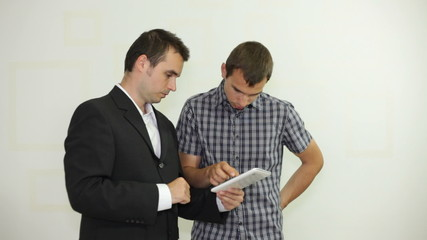 Two businessmen looking at electronic tablet