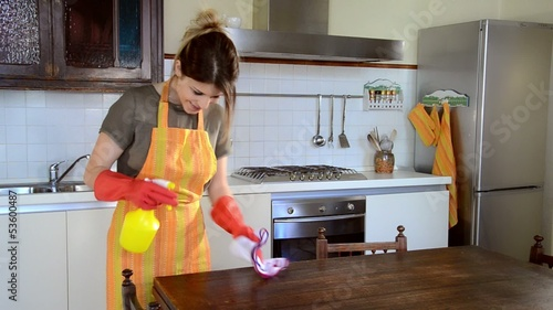 young housewife cleaning the furniture in the kitchen