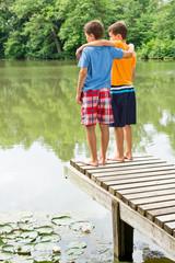 Zwei jugendliche Freunde blicken auf idyllischen Teich