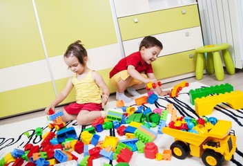 Two preschool children build castles with plastic cubes