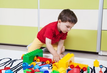Preschool boy who build towers with plastic cubes