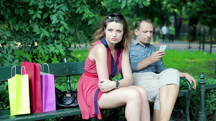 Young unhappy couple arguing in the park