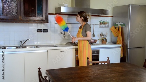 young woman cleaning the furniture in the kitchen